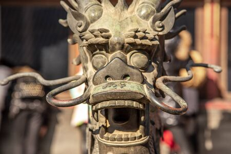 Chinese Dragon statue head with open jaws from Ming dynasty era, in the Forbidden City, Beijing, China