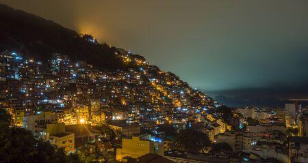 Night over Brazilian favelas on the hill with city downtown below, Rio De Janeiro, Brazil