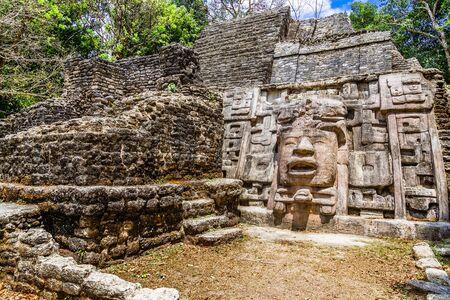 Ancienne pyramide de civilisation précolombienne maya en pierre ancienne avec visage sculpté et ornement caché dans la forêt, site archéologique de Lamanai, Orange Walk District, Belize