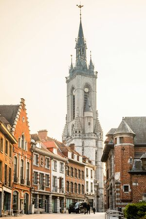 Tall medieval bell tower rising over the street with old european houses, Tournai, Walloon municipality, Belgium Banco de Imagens