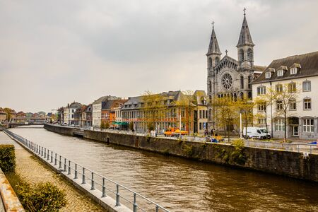 Escaut river and street with old belgian houses and facade of church of the Redemptorists of Tournai, Walloon municipality, Belgium