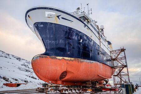 Fishing ships hulls in a dockyard on maintenance during the winter time, port of Nuuk, Greenland Banco de Imagens