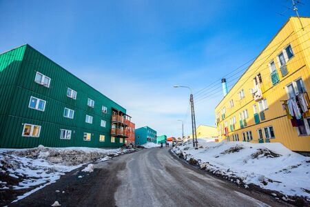 Muddy road with snow and living blocks with long low buildings in  Ilulissat city, Greenland Banco de Imagens - 135790203
