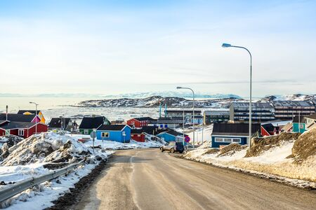 Arctic city center panorama with colorful Inuit houses on the rocky hills covered in snow with snow and mountain in the background, Ilulissat, Avannaata municipality, Greenland