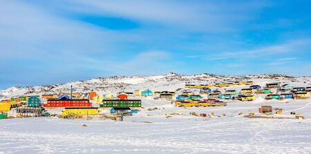 Arctic city center panorama with colorful Inuit houses on the rocky hills covered in snow, Ilulissat, Avannaata municipality, Greenland Banco de Imagens