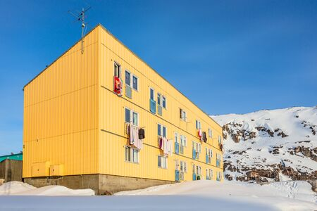 Arctic living residential house with snow hill in the background,  Ilulissat city, Greenland