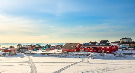 Arctic city center panorama with colorful Inuit houses at the fjord covered in snow, Ilulissat, Avannaata municipality, Greenland