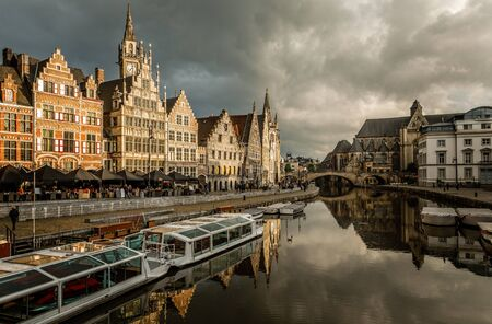 Graslei quay in the historic city center of Ghent, with boats bridge and old flemish buildings, Belgium