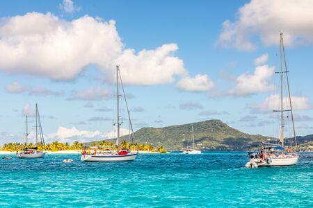 Turquoise sea and anchored yachts at Sandy beach island, near Carriacou island, Grenada, Caribbean sea Banco de Imagens - 139068924