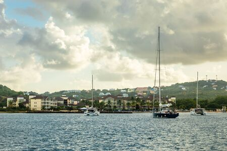 Offshore view of Rodney bay with yachts anchored in the lagoon and rich resorts in the background, Saint Lucia, Caribbean sea Banco de Imagens - 139573463