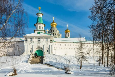 Snow and white walls, golden domes and a tower gate of New Jerusalem Monastery, Istra, Moscow region, Russia Stock Photo