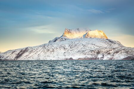Huge Sermitsiaq mountain covered in snow with sea in the foreground, nearby Nuuk city, Greenland Stock Photo