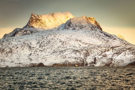 Huge Sermitsiaq mountain in a sunset rays covered in snow with blue sea and small fishing boat, nearby Nuuk city, Greenland