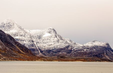 Snow topped mountains with Ukkusissat Little Malene peak and sea in the foreground, Nuuk, Greenland Stock Photo