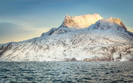 Huge Sermitsiaq mountain covered in snow with blue sea and small fishing boat, nearby Nuuk city, Greenland