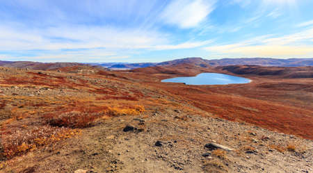 Autumn greenlandic orange tundra landscape with lakes and mountains in the background, Kangerlussuaq, Greenland Imagens