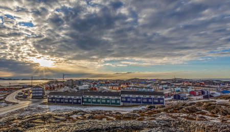 Grenlandic arctic city panorama with houses on the rocky hills in sunset city panorama. Nuuk, Greenland