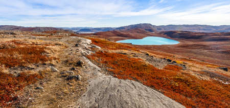 Autumn greenlandic orange tundra landscape with lakes and mountains in the background, Kangerlussuaq, Greenland Stock Photo