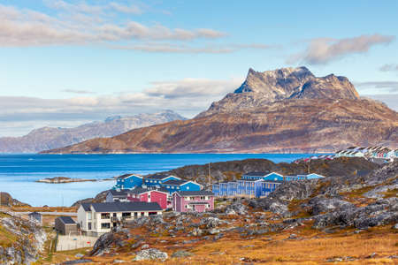 Inuit houses and cottages scattered across tundra landscape in residential suburb of Nuuk city with fjord and mountains in the background, Greenland Stock Photo