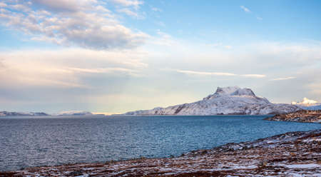 Frozen tundra landscape with cold greenlandic sea and snow Sermitsiaq mountain in the background, nearby Nuuk city, Greenland Stock Photo
