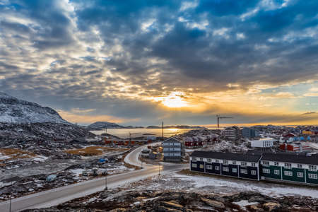 Arctic houses growing on the rocky hills in sunset panorama. Nuuk, Greenland