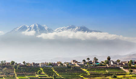 Snow capes of chachani Volcano over the fields and houses of peruvian city of Arequipa, Peru