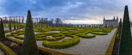 Frederiksborg castle , with ornamental landscape gardened shrubs in the foreground, Hillerod, Denmark