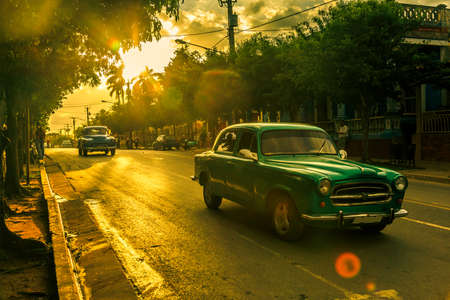 Retro cars on the streets of Vinales in sunset ray lights, Pinar Del Rio, Cuba