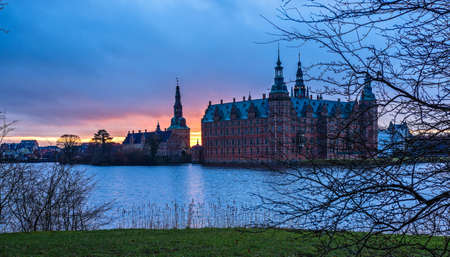 Frederiksborg castle on the sunset, with lake and tree in the foreground, Hillerod, Denmark Editorial
