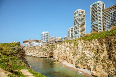 Downtown buildings and towers with rocks and sea in the foreground, Beirut, Lebanon