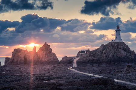 Road to La Corbiere lighthouse on the sea bottom in a low tide with cliff and sunset,  bailiwick of Jersey, Channel Islands