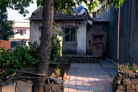 Stock photo of Indian village house or old cottage, old style house with traditional roof tile and small courtyard in front of house. Small plants and mango tree in courtyard at kolhapur India. Standard-Bild