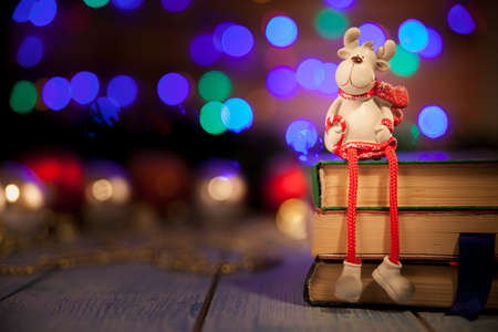 A toy deer sits on books in the background of a bokeh