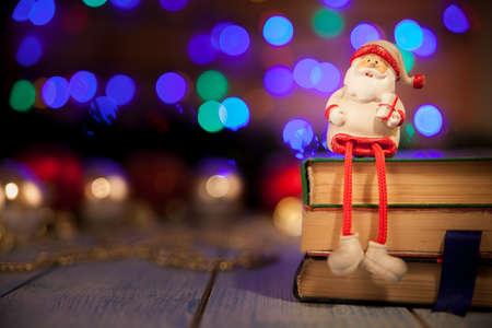 贈り物を持つおもちゃサンタクラウスは、背景ボケの本に座っています