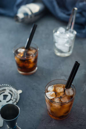 Alcohol cocktail with cola and ice with two cocktail tubes on a gray background in the background bar stock Stock Photo