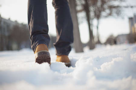 A man in red shoes and gray jeans is walking on the snow