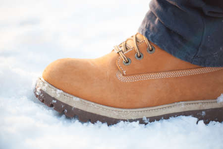 Red boots with lacing in the snow with dark jeans