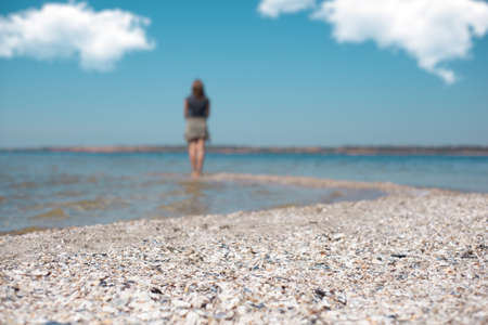 A girl stands on the edge of a sea beach and looks at the sea
