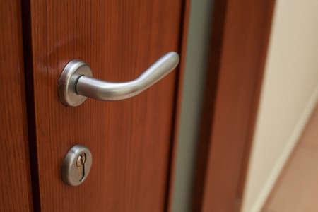Silvery door handle and lock on the brown wooden door Stock fotó
