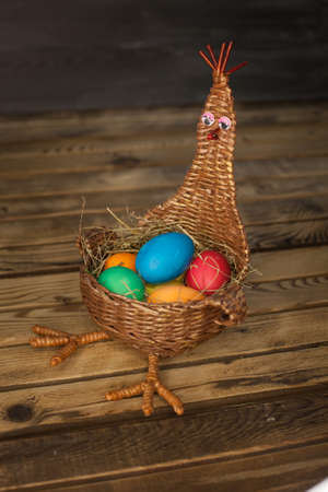 Wicker basket in the form of a chicken with colored Easter eggs on a wooden background Stock Photo