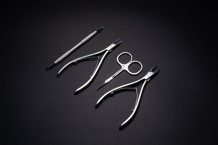 Manicure set of tools made of steel isolated on black background.