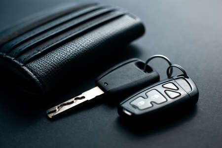 Black leather wallet with car key on a black background