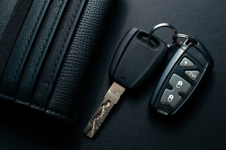 Black leather wallet with car key on a black background Фото со стока - 130135672