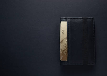 Black leather wallet with a gold credit card on an isolated black background Фото со стока