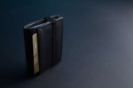 Black leather wallet with a gold credit card on an isolated black background Фото со стока - 130135682