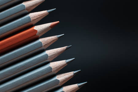 Red sharpened pencil between gray pencils isolated on black background
