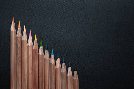 Sharpened pencils of different colors made of light wood isolated on black background.
