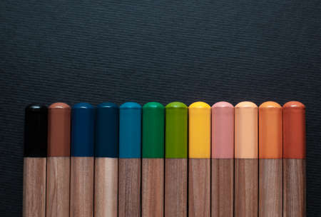 Not sharpened pencils of different colors isolated on a black background
