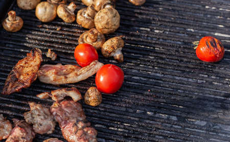 Tomato and mushrooms with meat grilled on a large grill