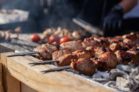 Skewered meat is cooked on hot coals by a cook in black uniform and gloves. Banco de Imagens